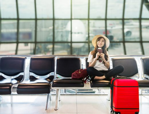 Happy Asian woman traveler holding the passport with suitcases a